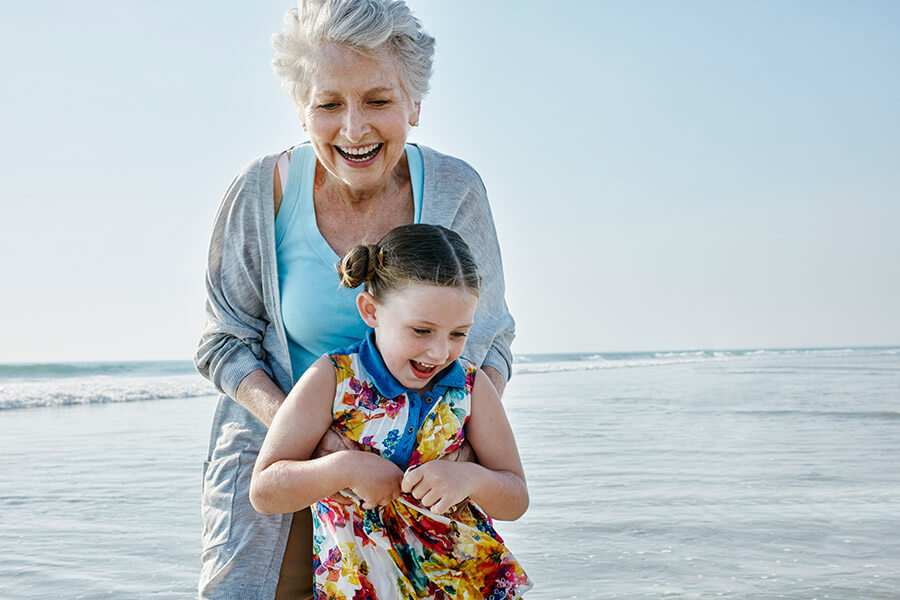 Grandmother and granddaughter playing by the shoreline