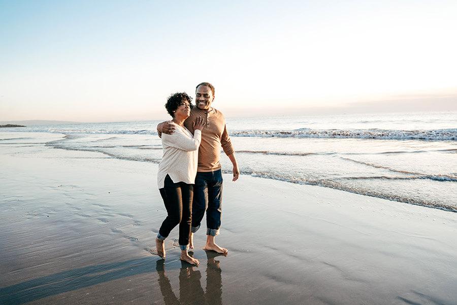 Couple walking barefoot along the shoreline