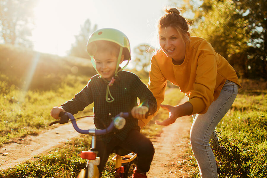 Mother teaching son to ride a bicycle